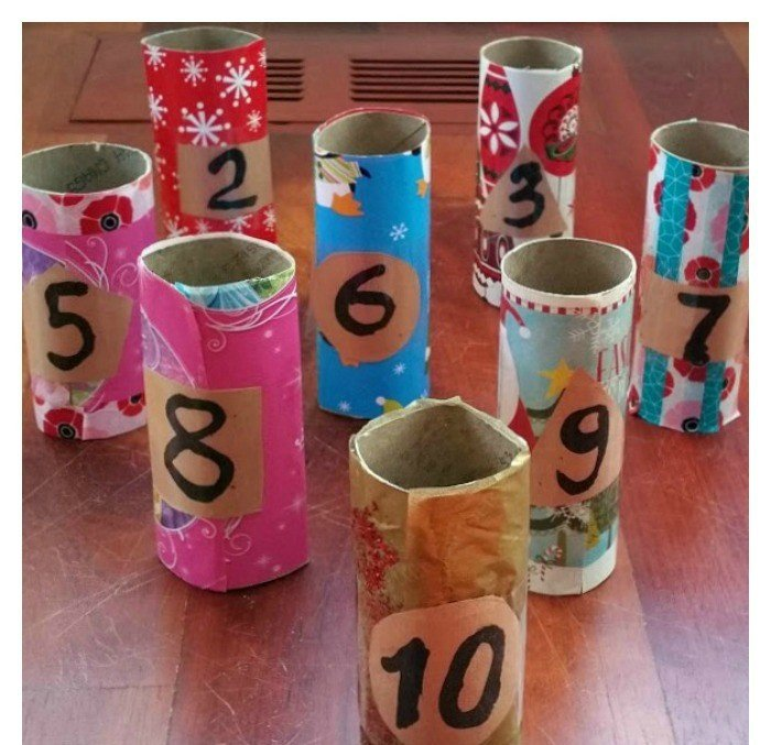 Turn your toilet paper rolls into bowling pins with a bit of wrapping paper and glitter.  Toddlers can practice rolling the ball toward the target.  Older kids can tape the numbers to the pins and practice some math.  #creativemath #mathmagic #mathfun #playfullearning #mathforlittlekids