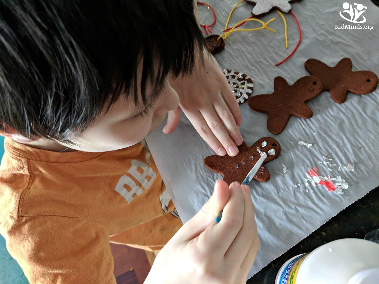 No-bake gingerbread man ornaments made with applesauce, cinnamon, and glue. Give it a try! Not only will they look gorgeous on your Christmas tree, but they're also great for gifting. #gingerbreadornaments #homemadeornaments #makingmemories #enjoyingtheday