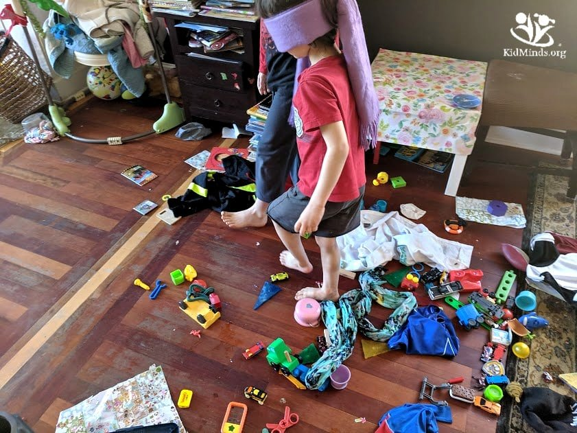 Toy Minefield is a blindfold game that will help your kids pick up their toys. Not only will your house get clean, but your kids will also practice directional words and listening skills. #familyfun #toomanytoys #siblingfun #growingupwithsiblings #siblingsday #cleaningupisfun #siblingsday #listeninggames #blindfoldgames