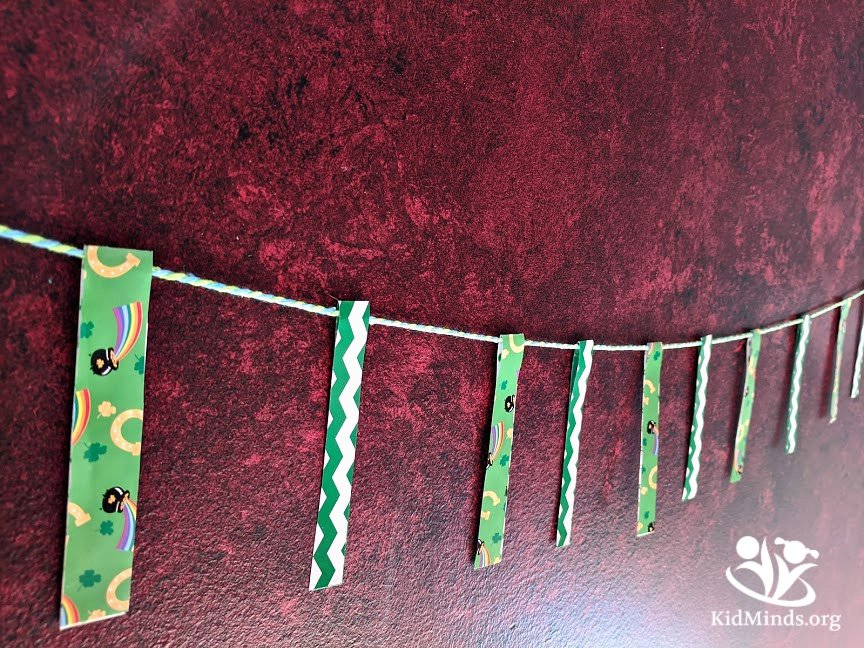 Combine fine motor skills practice with St. Patrick's Day theme for one of a kind DIY decor. This is one banner even very little kids can do on their own and feel proud of! #kidsactivities #finemotorskills #preschoolers #StPatricksDay #DIYbanner #craftykids #creativekids #funathomewithkids #creativelearning #handsonlearning #kidminds #earlylearning